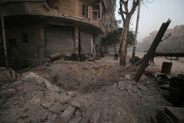 A man inspects damage near a hole in the ground after airstrikes on the rebel held al-Ansari neighbourhood of Aleppo, Syria October 2, 2016. REUTERS/Abdalrhman Ismail