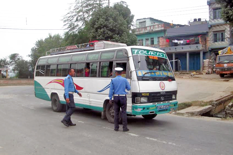 Traffic police checking a bus, in Damauli, Tanahun, on Friday, October 21, 2016. Photo: THT