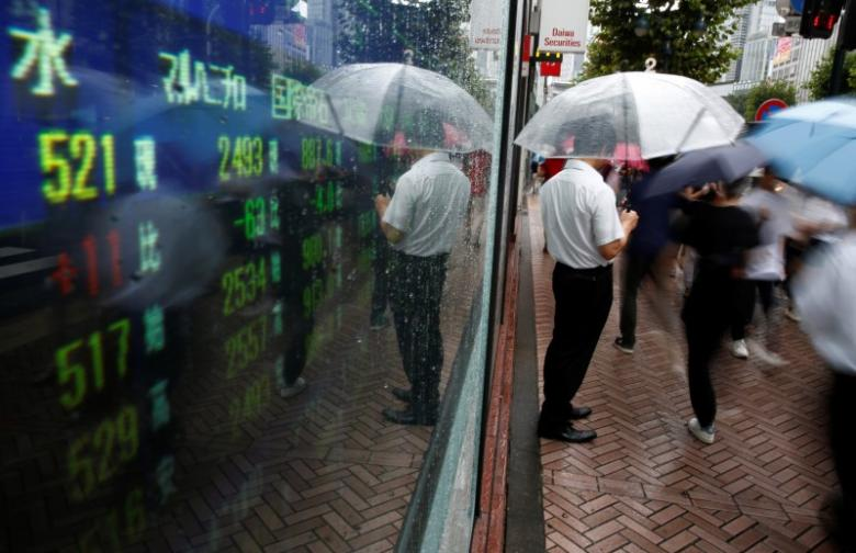 A man stands next to an electronic board showing stock prices in Tokyo, Japan, August 18, 2016. REUTERS/Kim Kyung-Hoon