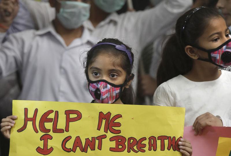 An Indian girls holds a banner during a protest against air pollution in New Delhi, India, Sunday, Nov. 6, 2016. Photo: AP