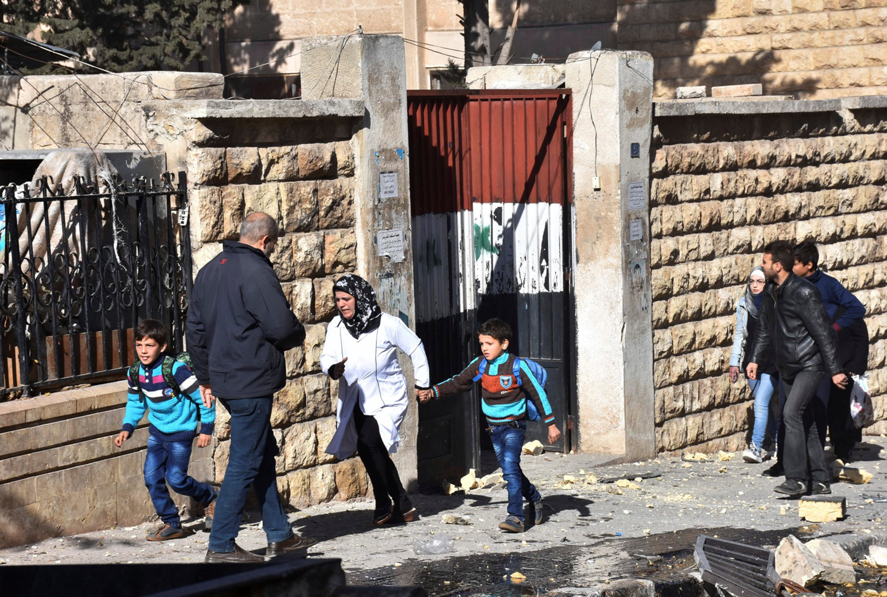 Schoolchildren evacuate a school after shelling by Syrian rebels on government-held western Aleppo, Syria in this handout picture provided by SANA on November 20, 2016. SANA/Handout via REUTERS ATTENTION EDITORS - THIS IMAGE WAS PROVIDED BY A THIRD PARTY. EDITORIAL USE ONLY. REUTERS IS UNABLE TO INDEPENDENTLY VERIFY THIS IMAGE.