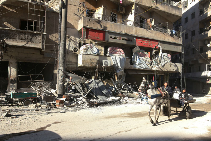 People ride a cart pulled by a horse near the damaged al-Hakeem hospital, in the rebel-held besieged area of Aleppo, Syria, on November 19, 2016. Photo: Reuters