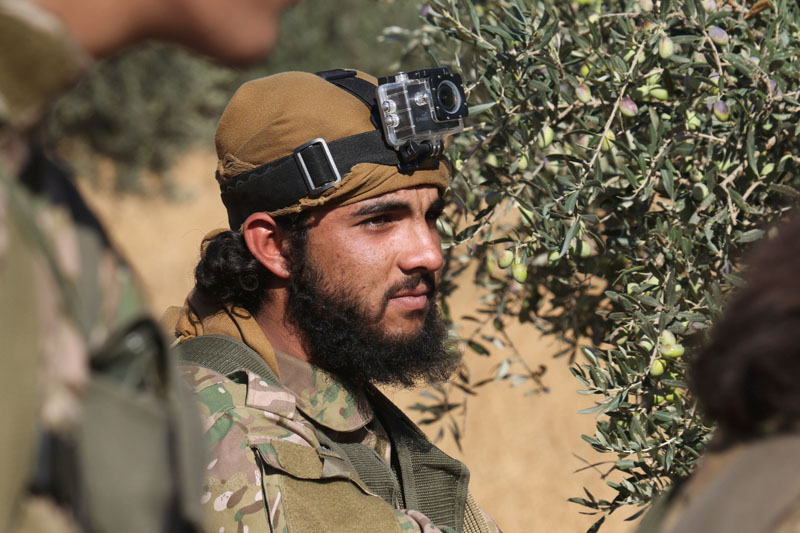 A rebel fighter with a camera attached to his head stands near an olive tree, western Aleppo city, Syria, on November 3, 2016. Photo: Reuters