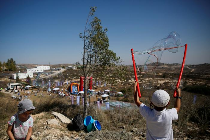 Children play during an event organised to show support for the Jewish settler outpost of Amona in the West Bank, that was built without Israeli state authorisation and which Israel's high court ruled must be evacuated and demolished by the end of the year as it is built on privately-owned Palestinian land, October 20, 2016. REUTERS/Ronen Zvulun/File Photo
