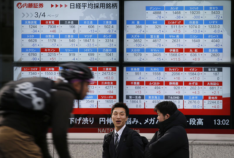 People chat in front of the electronic board showing Nikkei stock prices in Tokyo, on Monday, November 28, 2016. Photo: AP
