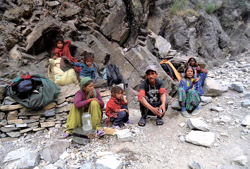 Locals taking rest on their way home after  purchasing salt from Kolti depot, in Bajura, on Saturday, November 19, 2016. Photo: THT