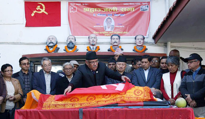 Prime and CPN Maoist Centre Chairman Pushpa Kamal Dahal drapes the party flag over lawmaker Bhakti Prasad Pandey's body during a condolence meeting held at the party Central Office in Parisdanda, Kathmandu on Tuesday, November 15, 2016. Photo: PM's Secretariat