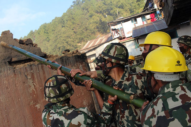 Nepal Army personnel demolish houses destroyed by a fire on November 20 in Bhojpur district headquarters, on November 26, 2016. Photo: Niroj Koirala