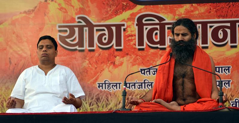 Baba Ramdev (right) and Acharya Balkrishna teach yoga.