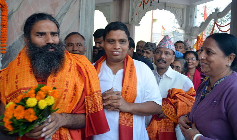 Baba Ramdev (left) and Acharya Balkrishna exchange greetings with public while visiting Gahawamai Temple.