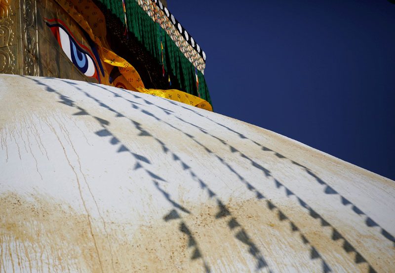 A Buddha eye is seen behind the prayer flags during the prayers to purify the renovated Bouddhanath stupa. Photo: Reuters