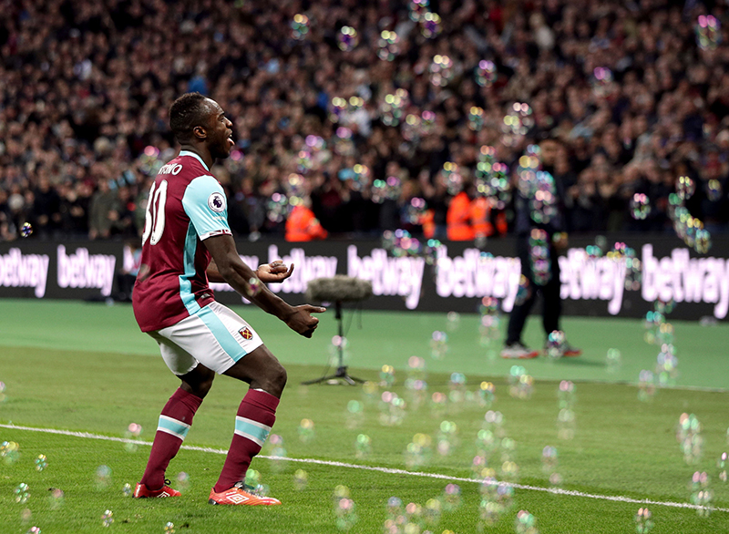 Bubbles float by as West Ham United's Michail Antonio celebrates scoring his side's first goal of the game against Stoke City during their English Premier League soccer match between West Ham and Stoke City at London Stadium, in London, Saturday Nov. 5, 2016. (Yui Mok / PA via AP)