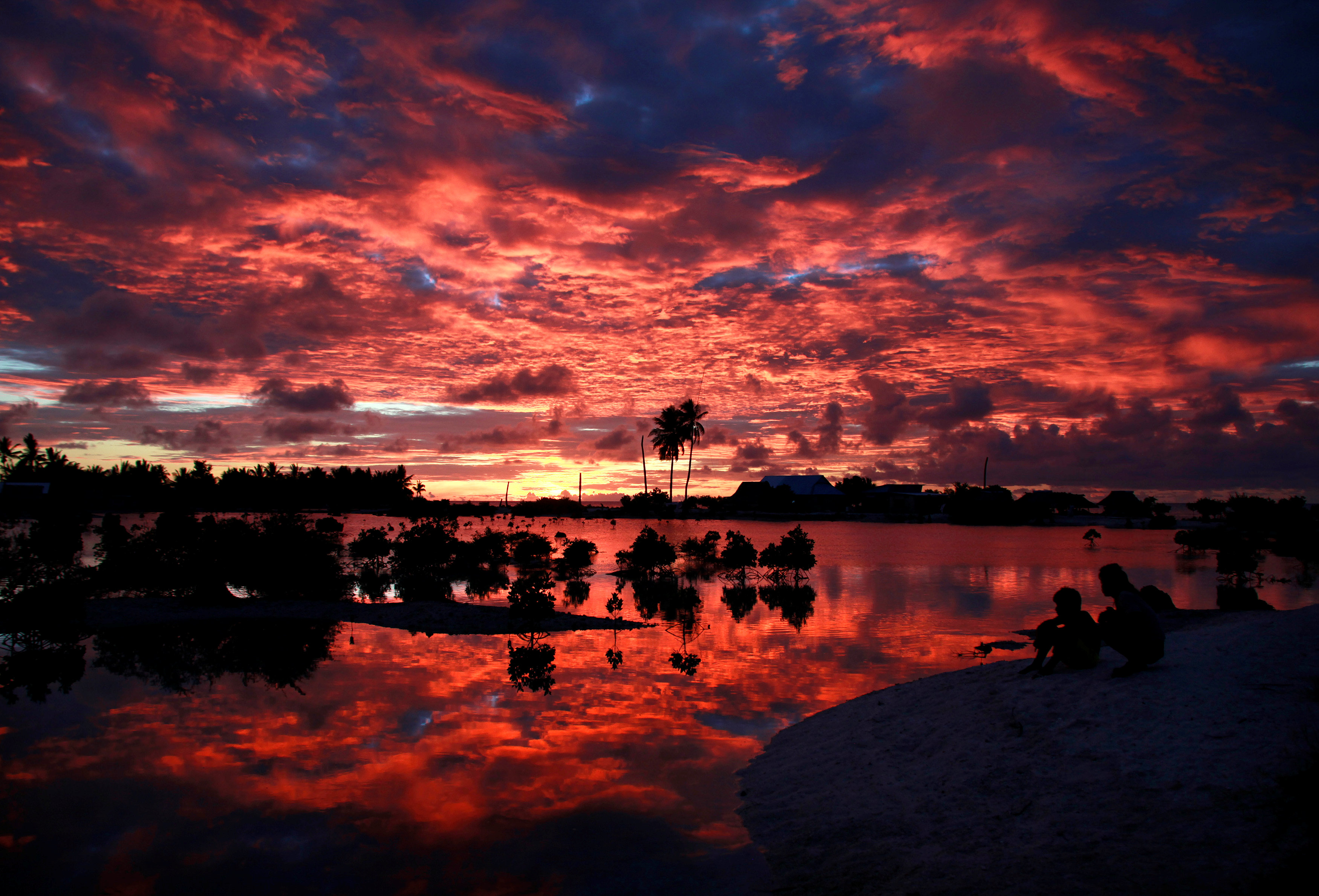 Villagers watch the sunset over a small lagoon near the village of Tangintebu on South Tarawa in the central Pacific island nation of Kiribati May 25, 2013.  REUTERS/David Gray/File Photo