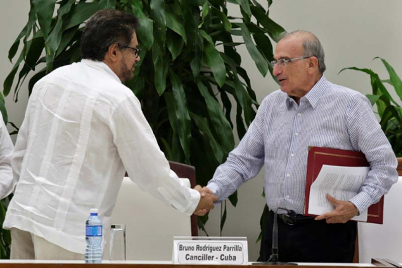 Colombia's FARC lead negotiator Ivan Marquez (L) and Colombia's lead government negotiator Humberto de la Calle shake hands after signing a new peace deal to end their 52-year war in Havana, Cuba, on November 12, 2016. Photo: Reuters