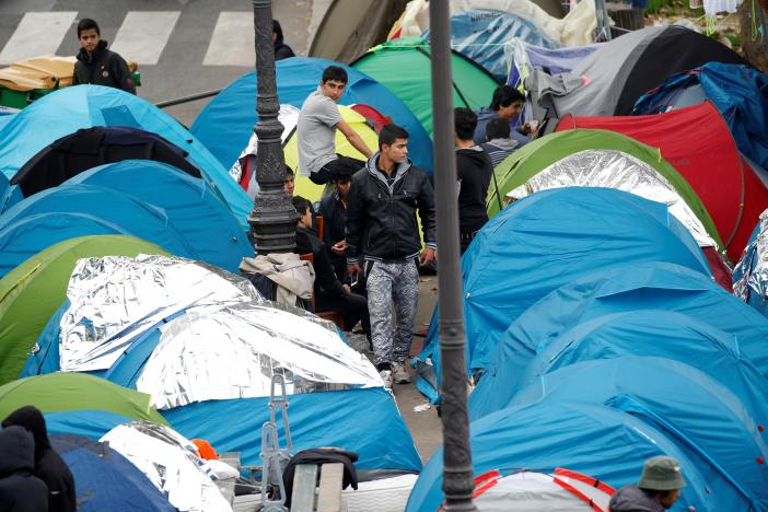 Migrants stand near their tents at a makeshift migrant camp on a street near the metro stations of Jaures and Stalingrad in Paris.  REUTERS/Charles Platiau