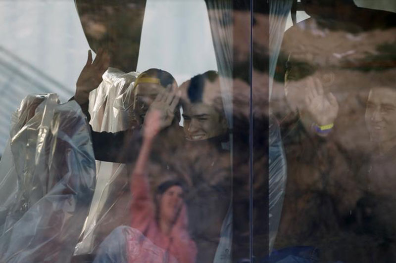 Migrant minors wave from a bus before their transfer by French authorities to reception centres across the country at the end of the dismantlement of the camp called the ''Jungle'' in Calais, France, on Wednesday, November 2, 2016. Photo: Reuters