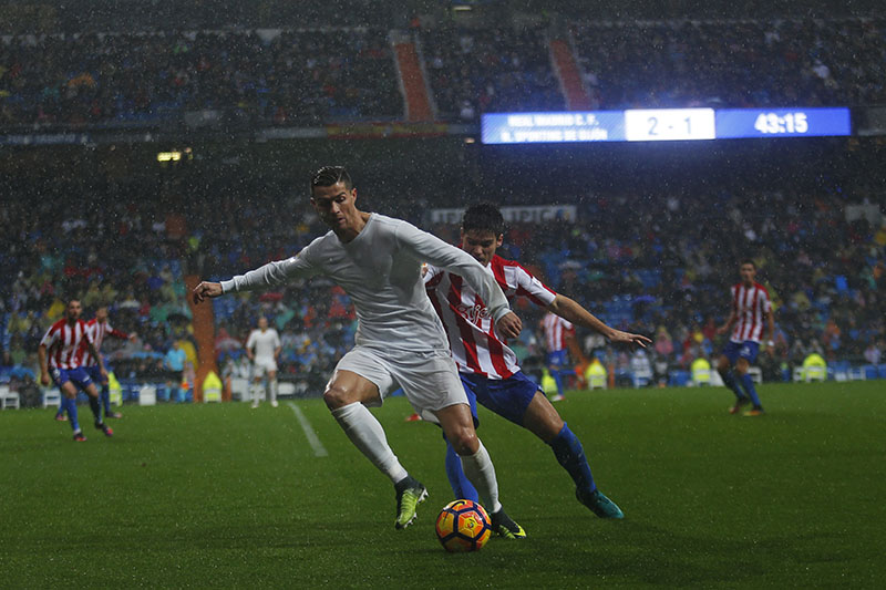 Real Madrid's Cristiano Ronaldo (left) vies for the ball with Sporting's Jorge Mere during a Spanish La Liga soccer match between Real Madrid and Sporting at the Santiago Bernabeu stadium in Madrid, on Saturday, November 26, 2016. Ronaldo scored twice in Real Madrid's 2-1 victory. Photo: AP