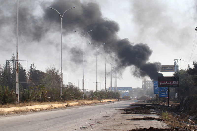 Smoke rises near a damaged road in Dahiyet al-Assad, west Aleppo city, Syria, on October 30, 2016. Photo: Reuters
