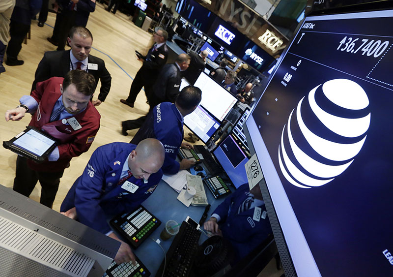 FILE - Traders gather at the post that handles AT&T on the floor of the New York Stock Exchange, on Monday, May 19, 2014. Photo: AP