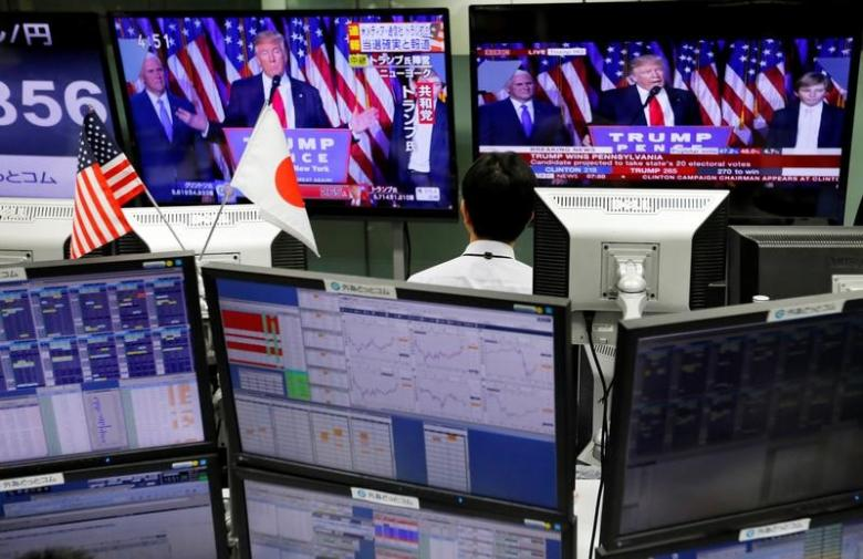 An employee of a foreign exchange trading company looks at monitors showing U.S. President elect Donald Trump speaking on TV news in Tokyo, Japan, November 9, 2016.   REUTERS/Toru Hanai