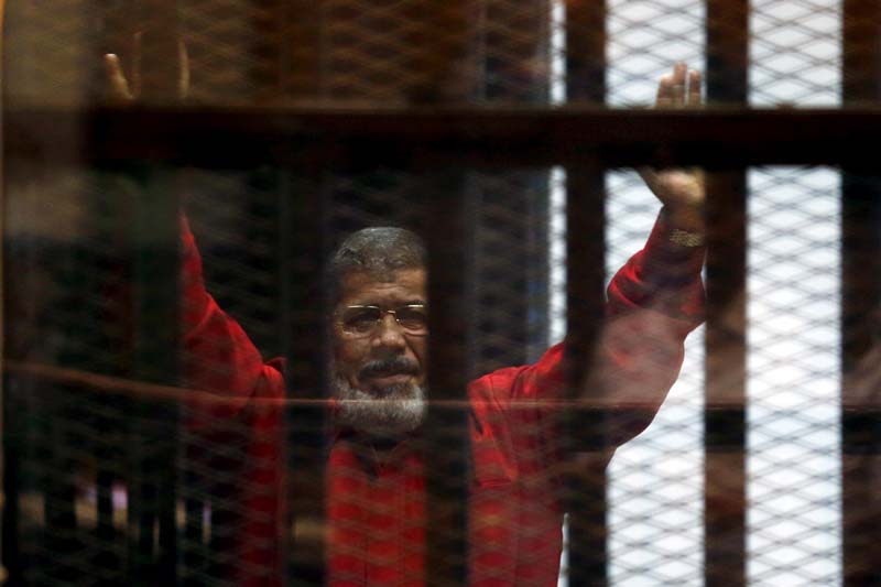 File- Former Egyptian President Mohamed Mursi greets his lawyers and people from behind bars at a court, during his court appearance with Muslim Brotherhood members on the outskirts of Cairo, Egypt, on June 21, 2015. Photo: Reuters