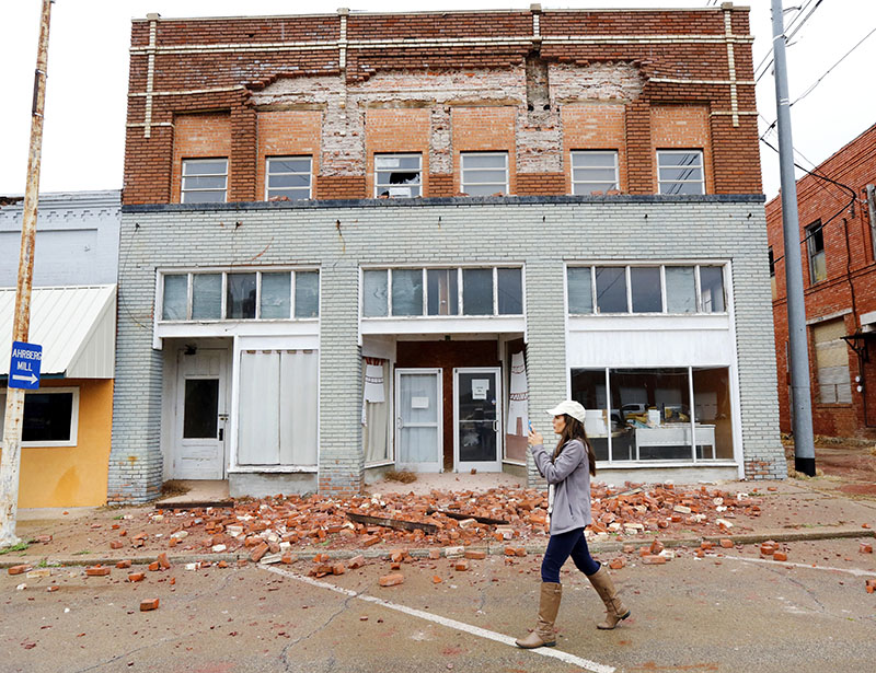 A television reporter takes video as she walks past a damaged building in Cushing, Oklahoma, caused by Sunday night's 5.0 magnitude earthquake, on Monday, November 7, 2016. Photo: Jim Beckel The Oklahoman via AP