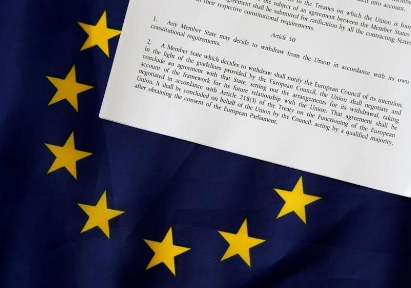 File - Article 50 of the EU's Lisbon Treaty that deals with the mechanism for departure is pictured with an EU flag following Britain's referendum results to leave the European Union, in this photo illustration taken in Brussels, Belgium, on June 24, 2016. Photo: Reuters