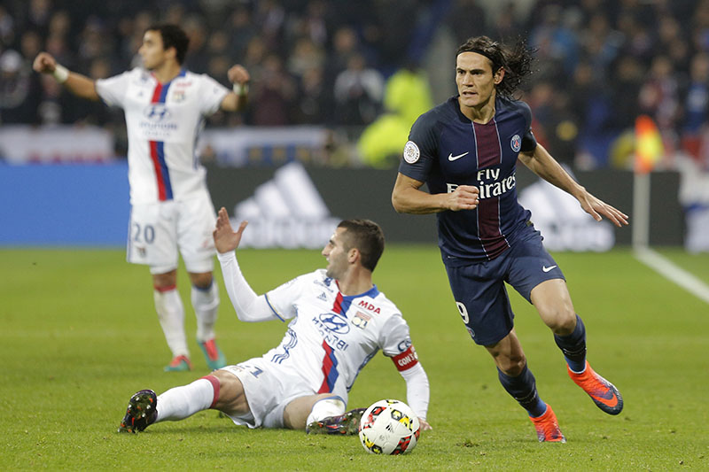 Paris Saint Germain's Edinson Roberto Cavani (right) controls the ball after a challenge with Lyon' players during their French League One soccer match, in Decines, near Lyon, central France, on Sunday, November 27, 2016. Photo: AP