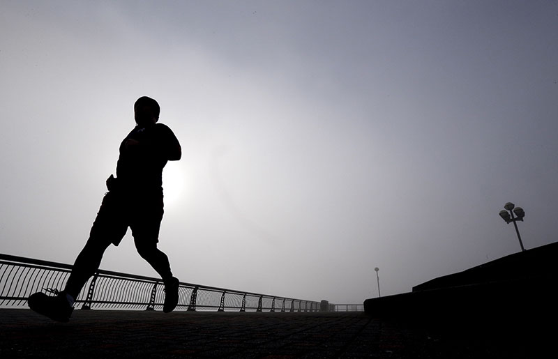 FILE - A man jogs at Pier A Park in Hoboken, New Jersey Clean living can greatly lower your risk for heart disease even if your genes are heavily stacked against you, on Wednesday, January 15, 2014. Photo: AP