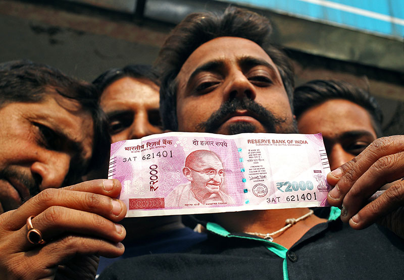 A man displays a new 2000 Indian rupee banknote after withdrawing from a bank in Jammu on Friday, November 11, 2016. Photo: REUTERS