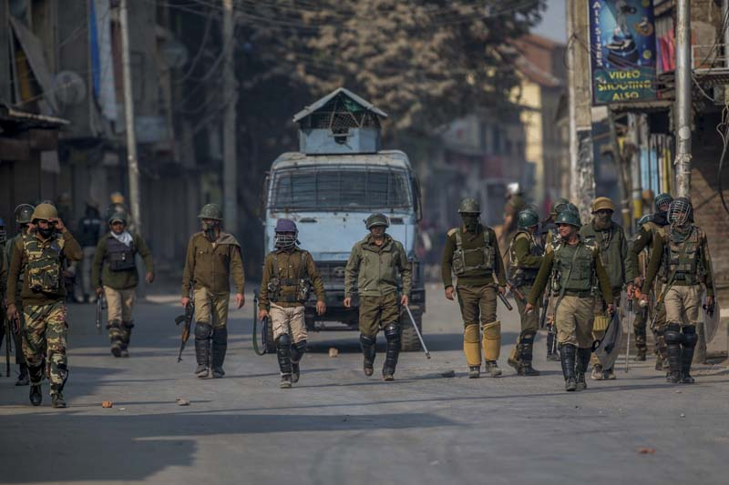 Indian police and paramilitary soldiers petrol a deserted street during a raid to arrest suspected protesters on the outskirts of Srinagar, Indian-controlled Kashmir, on November 2, 2016. Photo: AP