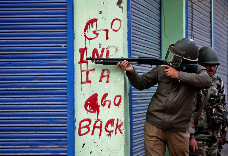 An Indian policeman aims his gun during an anti-India protest in Srinagar, on November 4, 2016. Photo: Reuters