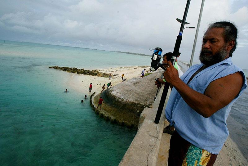 FILE - A man fishes on a bridge on Tarawa atoll, Kiribati, on March 30, 2004. Photo: AP