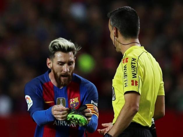 Football Soccer - Spanish La Liga Santander - Sevilla v Barcelona - Ramon Sanchez Pizjuan Stadium, Seville, Spain - 6/11/2016. Barcelona's Lionel Messi holds one of his boots. REUTERS/ Marcelo del Pozo
