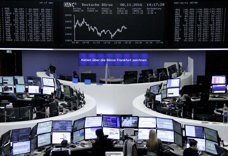 Traders work at their desks in front of the German share price index, DAX board, at the stock exchange in Frankfurt, Germany, on Tuesday, November 8, 2016. Photo: Reuters