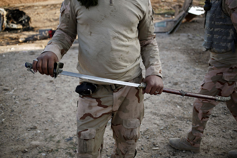 An Iraqi soldier holds up a sword he found, which he says is similar to the kind used by Islamic State militants for beheadings, at the front line in the Intisar disrict of eastern Mosul, Iraq November 4, 2016. Photo: REUTERS
