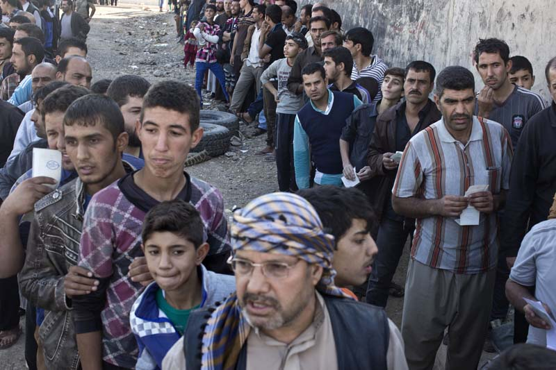 People queue to receive aid packages in Gogjali, on the eastern edge of Mosul, Iraq, on Thursday, November 3, 2016. Photo: AP