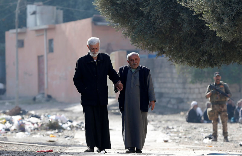 Two men hold hands as an Iraqi Special forces intelligence team searches for Islamic State fighters in Mosul, Iraq, on November 27, 2016. Photo: Reuters