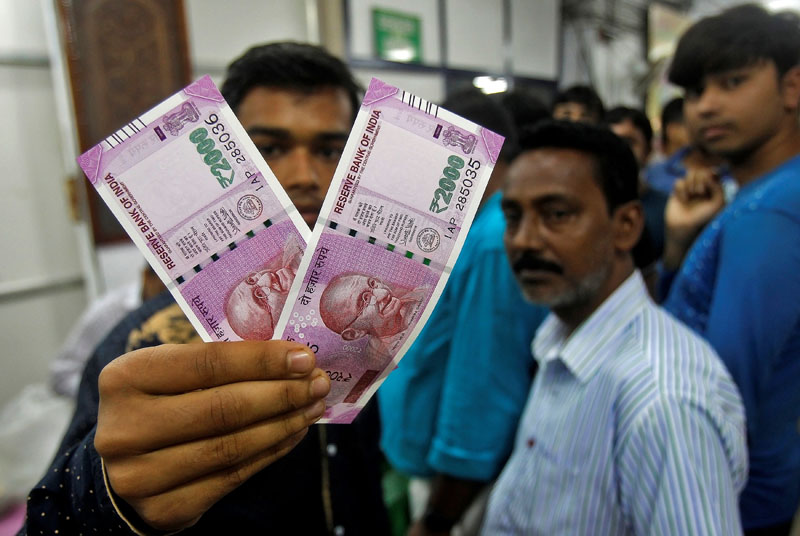 A man displays the new 2000 Indian rupee banknotes after withdrawing them from State Bank of India in Agartala, India, on November 11, 2016. Photo: Reuters
