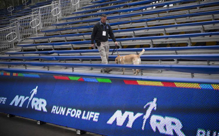 A security officer and a bomb sniffing dog patrol bleachers set up near the finish of the New York City Marathon, in New York's Central Park, October 31, 2014. REUTERS/Mike Segar/File Photo