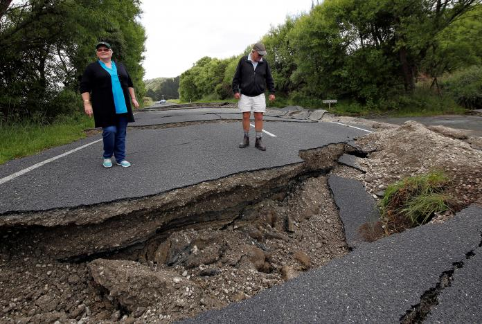 Local residents Chris and Viv Young look at damage caused by an earthquake along State Highway One, south of the township of Blenheim on South Island. REUTERS/Anthony Phelps