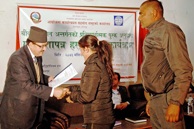 PACT sub-project monitoring committee chairman Yogendra Singh Karki distributes grant agreements to grant recipients, in Kathmandu on Wednesday, November 30, 2016.