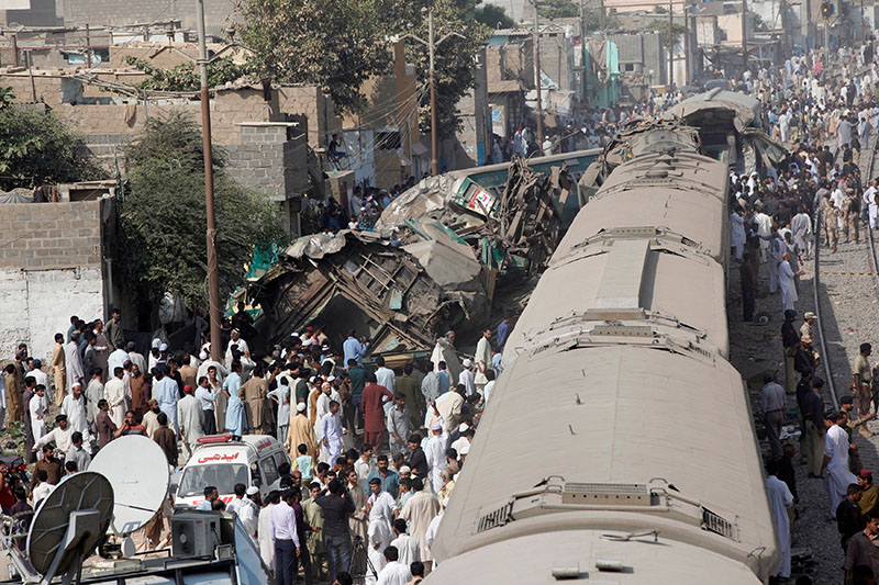 Spectators watch as rescue workers search a train which crashed in Karachi, Pakistan on Thursday, November 3, 2016. Photo: REUTERS