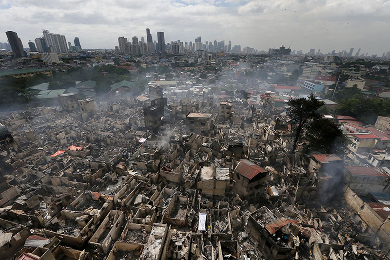 Smoke continues to rise from the Addition Hills community in suburban Mandaluyong city east Manila, Philippines, following an overnight fire that destroyed hundreds of homes and rendered more than 5,000 people homeless on Monday, November 14, 2016. Photo: AP