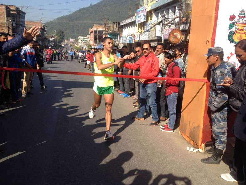 TACu2019s Rajan Khatri touches the finishing line of the first nNational Marathon Competition in Hetauda on Thursday. THT
