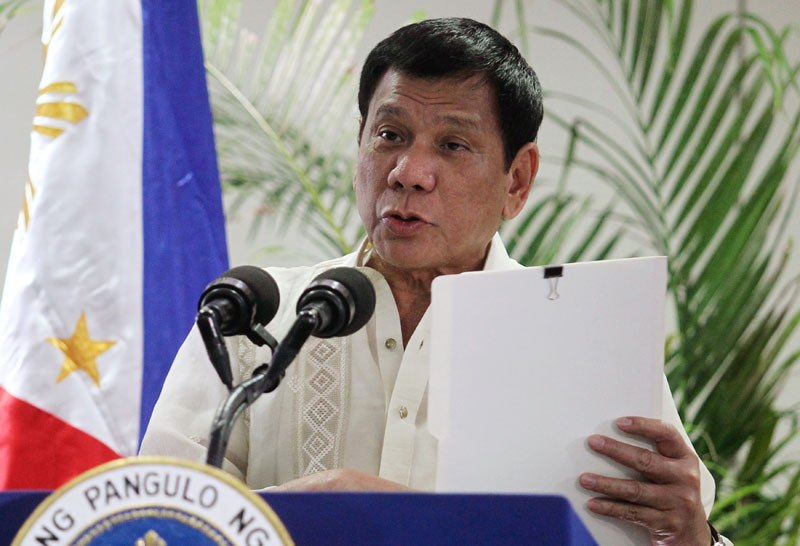 Philippine President Rodrigo Duterte holds a copy of his speech as he speaks after arriving from Malaysia, at Davao International airport in Davao city in southern Philippines, on November 11, 2016. Photo: Reuters
