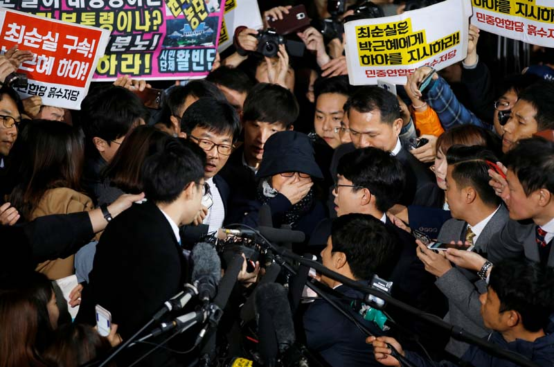 Choi Soon-sil (C), who is involved a political scandal, reacts as she is surrounded by media and protesters upon her arrival at a prosecutor's office in Seoul, South Korea, on October 31, 2016. Photo: Reuters
