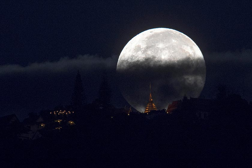 The supermoon is partly covered by clouds as it sets behind Wat Phrathat Doi Suthep in the northern capital of Chiang Mai, Thailand, November 15, 2016. Photo: Reuters