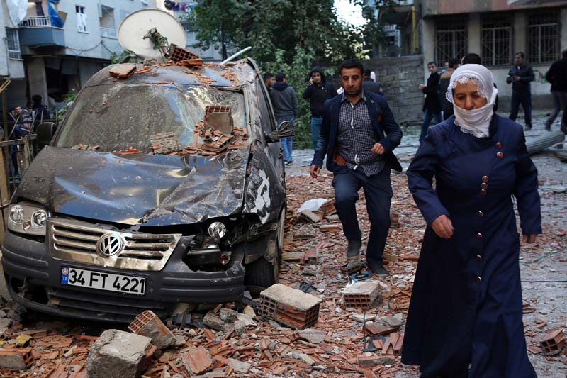 People walk past a damaged car after a blast in the Kurdish-dominated southeastern city of Diyarbakir, Turkey, on Friday, November 4, 2016. Photo: Reuters