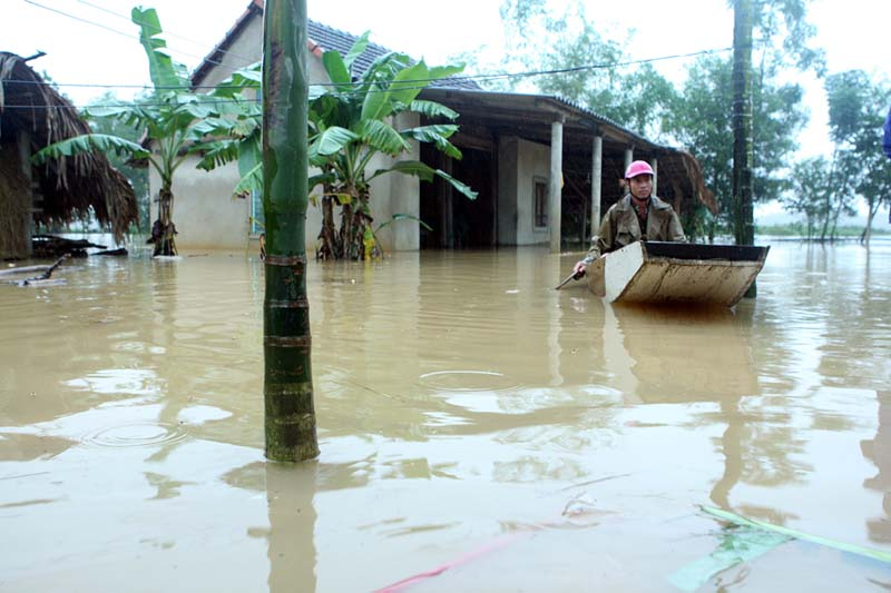 A man paddles a boat near his submerged house during a flood in Vietnam's central Ha Tinh province, on October 15, 2016. Photo: AP